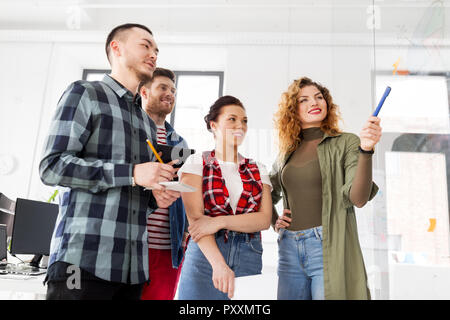 creative team with chart on glass board at office - Stock Photo