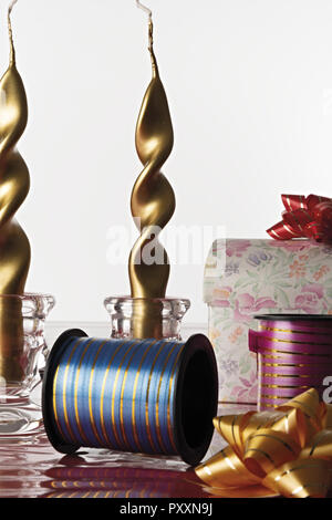 gold color party candles with box and ribbons in front - Stock Photo