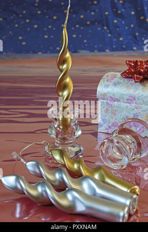 holiday candles gold color and silver glass candle holder with box and ribbons in front - Stock Photo
