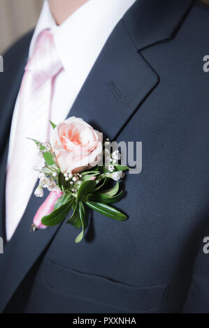 A pink rose boutonniere on a men's navy jacket. - Stock Photo