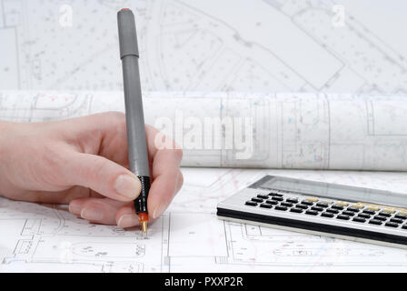 Woman's hand holding rapidograph, architectural plans in background - Stock Photo