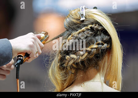Hairdresser creates hairdo by curling iron in a hair salon - Stock Photo