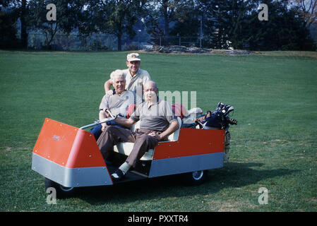 1970s, two male golfers sitting in an unusual three-wheeled electric golf cart, with a tiller-based steering control, USA. It was in the 1950s that the golf cat or kart began to become more popular with golfers, in particular the more elderly players. The early electric golf cars were used on golf courses with a fairly flat terrain as their batteries had a short life. - Stock Photo