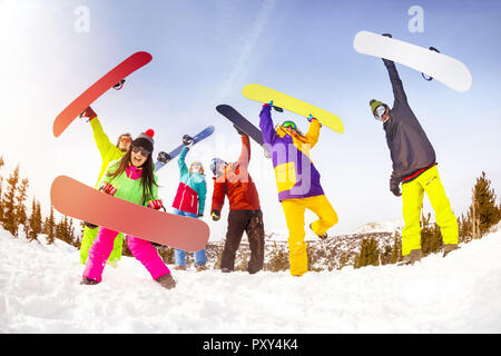 Big group of friends snowboarders are having fun with snowboards on mountain top of ski resort - Stock Photo