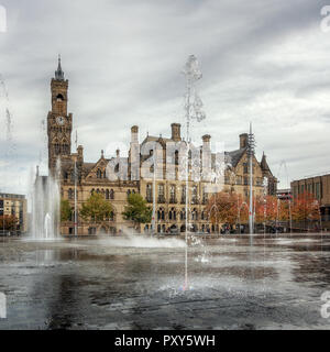 Bradford City Hall with fountains in the middle of Centenary Square mirror pool on an autumnal day with remembrance poppies in the trees - Stock Photo