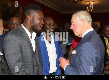 The Prince of Wales talking with Ghanian Music duo Reggie Zippy and Bollie Babeface known as 'Reggie 'n' Bollie' during a reception at St James's Palace, London, ahead of his visit to The Gambia, Ghana and Nigeria. - Stock Photo