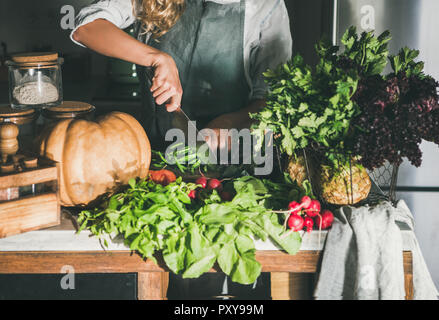 Female in apron cutting various vegetable ingredients on counter - Stock Photo