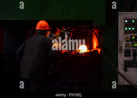 Industrial Worker at the factory welding closeup. Hot iron in smeltery held by a worker. Smelting of the metal in the foundry. Heavy forging steelmaki - Stock Photo