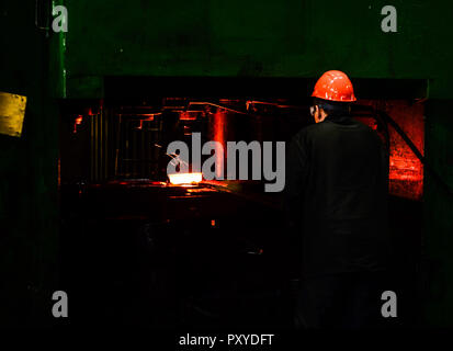 Hot iron in smeltery held by a worker. Iron melting recycling work. Heavy forging steelmaking plant and steelmaking workshop. - Stock Photo