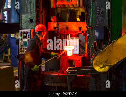 Hot iron in smeltery held by a worker. High precision hot forging product, automotive part production by hot forging process, automatice line hot forg - Stock Photo