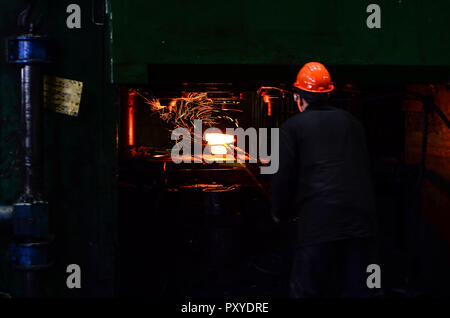 Hot iron in smeltery held by a worker. Iron melting recycling work. Metallurgical production, manufacturing premises, workshop at the plant, blast fur - Stock Photo