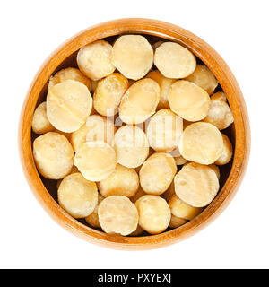 Roasted and salted macadamia nuts in wooden bowl. Also called Queensland, bush, maroochi, bauple or Hawaii nut. Healthy snack. Macro photo. - Stock Photo