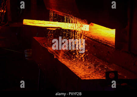Hot iron in smeltery held by a worker. Iron melting recycling work.  High temperature in the melting furnace. Metallurgical industry. - Stock Photo