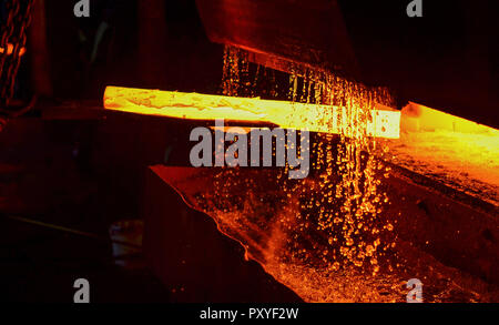 Hot iron in smeltery held by a worker. Melting of metal in a steel plant. High temperature in the melting furnace. Metallurgical industry. Factory for - Stock Photo