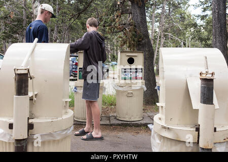 Two young men putting their trash into recylcling bins in Yellowstone National Park, Wyoming, USA - Stock Photo