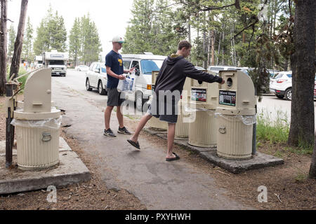 Two young men putting their trash into separate recylcling bins in Yellowstone National Park, Wyoming, USA - Stock Photo