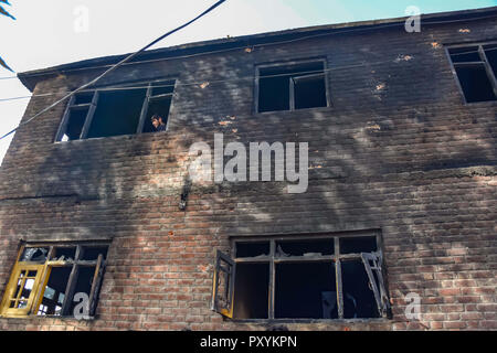 October 24, 2018 - Srinagar, Jammu & Kashmir, India - Kashmiri man seen looking out from a damaged window of damaged house after a gun battle.Indian troops laid a siege around Nowgam area in Srinagar following a tip that Rebels were hiding there, police said. The searches by troops triggered an exchange of gunfire resulting in the deaths of two Kashmiri rebels and injuries to six Indian policemen. Credit: Idrees Abbas/SOPA Images/ZUMA Wire/Alamy Live News - Stock Photo