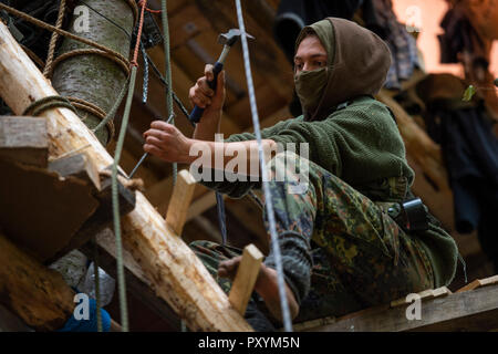 Kerpen, Germany. 24th Oct, 2018. 24 October 2018, Germany, Kerpen: An activist is building a tree house in the Hambach forest. Credit: Christophe Gateau/dpa/Alamy Live News - Stock Photo
