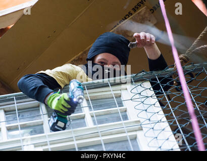 Kerpen, Germany. 24th Oct, 2018. 24 October 2018, Germany, Kerpen: An activist is in the Hambach forest on a tree house with a cordless screwdriver. Credit: Christophe Gateau/dpa/Alamy Live News - Stock Photo