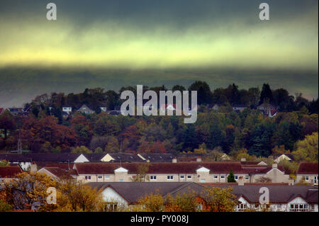 Glasgow, Scotland, UK, 25th October, 2018. UK Weather: Cloudy day wit rolling mist from the Kilpatrick hills into the leafy suburb of Bearsden villas among-st the trees with the roofs  of council houses in the foreground. Credit: gerard ferry/Alamy Live News - Stock Photo