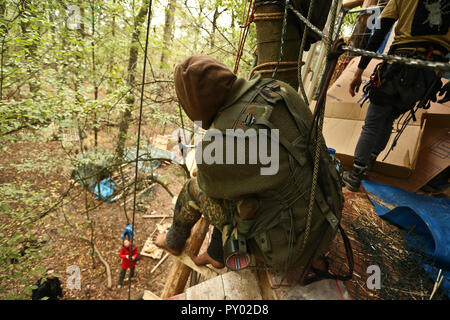 Kerpen, Germany. 24th Oct, 2018. In the Hambach Forest, a masked activist is building a new tree house barefoot at a height of about eight metres. This is where the tree village of Endor is built. Credit: David Young/dpa/Alamy Live News - Stock Photo