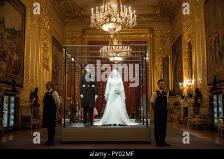 Windsor, UK. 25th October, 2018. IMAGE EMBARGOED FOR PUBLICATION UNTIL 00:01 BST, FRIDAY, 26 OCTOBER. Windsor Castle staff members pose next to the Duchess of Sussex's wedding dress, created by the British designer Clare Waight Keller, Artistic Director at the historic French fashion house Givenchy, and the Duke of Sussex's frockcoat uniform of the Household Cavalry, which will go on display from 26th October 2018 to 6th January 2019 as part of a special exhibition entitled 'A Royal Wedding: The Duke and Duchess of Sussex'. Credit: Mark Kerrison/Alamy Live News - Stock Photo