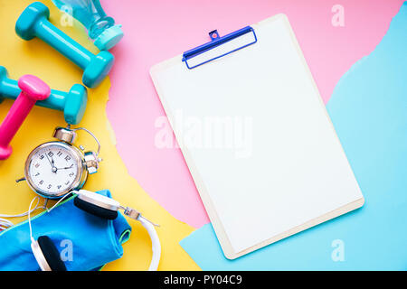 Clipboard near pile of sports equipment - Stock Photo
