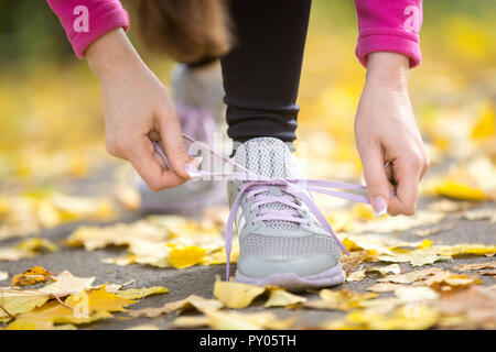 Hands tying trainers shoelaces on the autumn pave, full of yellow leaves. Concept photo, horizontal, closeup - Stock Photo