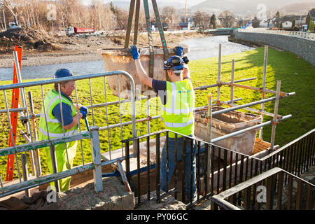Following the disastrous floods of 2009 in Cumbria, the Environment Agency are spending ÂỲÂẀÂỲ£6.1 million on a new flood defence scheme for Keswick. This shot shows construction workers man handling cement to build the new defences. Despite costing over ÂỲÂẀÂỲ£6million, they were completely overtopped by the floods from Storm Desmond, 6 years later. - Stock Photo