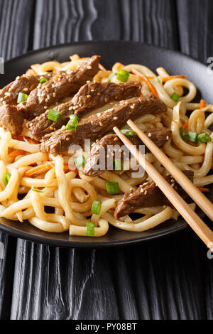 Delicious teriyaki beef with udon noodles, carrots and green onions close-up on a plate on the table. vertical. - Stock Photo