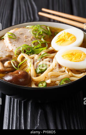 Asian soup with udon noodles, pork, eggs, shiitake and onions close-up in a bowl on the table. vertical - Stock Photo