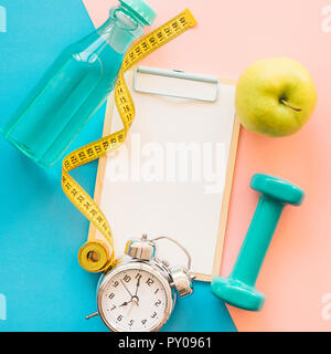 Weight loss composition with clipboard tape measure and bottle - Stock Photo