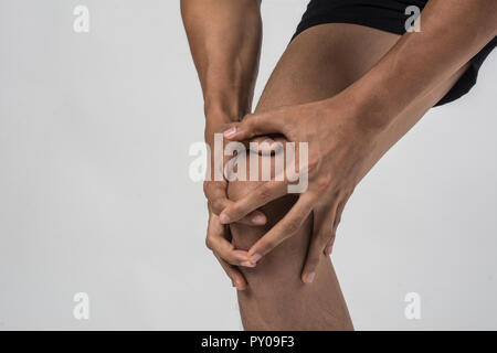 Young sport man with strong athletic legs holding knee with his hands in pain after suffering ligament injury  isolated on white. - Stock Photo