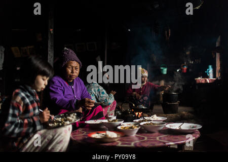Three generation family eating together in small rural house, Myanmar, Shan, Myanmar - Stock Photo