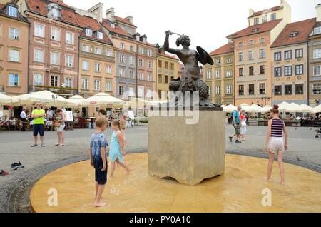 Warsaw, Poland - July 30, 2018: Kids playing at the water around the Little Mermaid statue at the Market Square in the old town of Warsaw, Poland. - Stock Photo