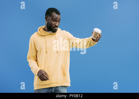 young african american man offering disposable coffee cup isolated on blue background - Stock Photo