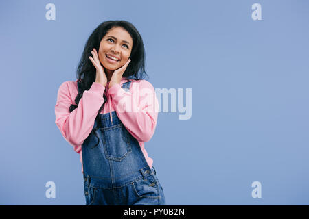 dreamy young african american woman with hands on cheeks isolated on blue background - Stock Photo