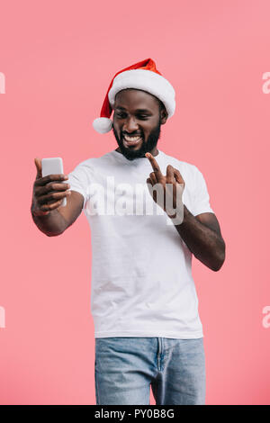 portrait of smiling african american man in santa claus hat with smartphone showing middle finger isolated on pink - Stock Photo