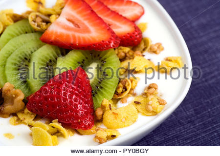 This is a gluten-free version of granola - nuts, corn flakes and various sees, with fresh kiwi, strawberry and plain yogurt. - Stock Photo