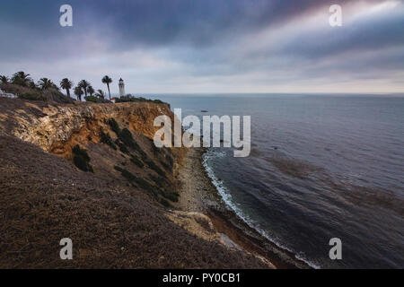 Beautiful coastal view of Point Vicente Lighthouse atop the steep cliffs of Rancho Palos Verdes, California on a cloudy day with dramatic sky - Stock Photo