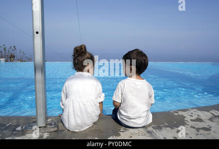 Little boy and girl sitting next to each other on the border of a swimming pool - Stock Photo