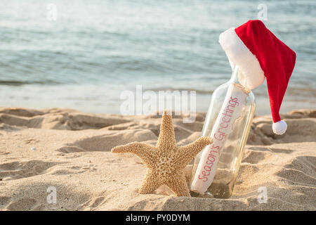 Christmas Santa hat on Seasons Greetings message in a bottle with starfish in beach sand and water background - Stock Photo
