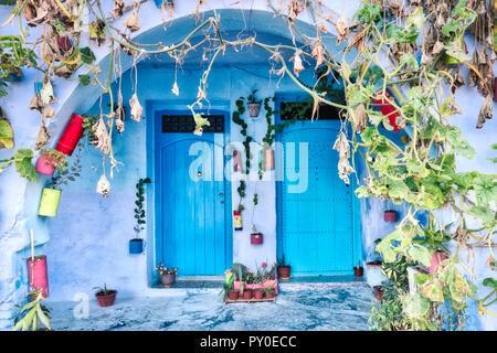 Typical blue facade with ancient doors decorated with pots in Chefchaouen, Morocco - Stock Photo