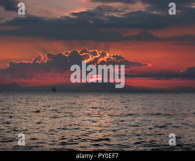 Distant view of silhouette of sailboat in sea at sunset, Boracay, Aklan, Philippines - Stock Photo