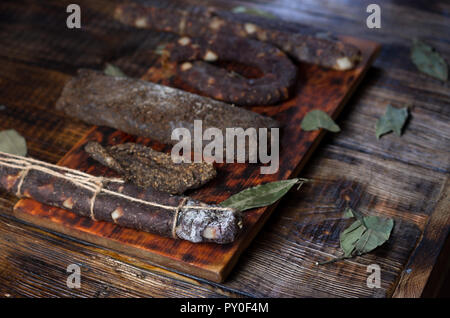 Dried meat on the kitchen board. Dark composition. - Stock Photo