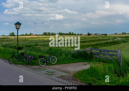 Netherlands, Zaanse Schans, a bicycle parked on the side of the road below lamp post near meadow fence - Stock Photo