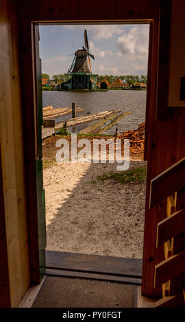 Netherlands, Zaanse Schans, a windmill on the side of a river viewed through a window - Stock Photo