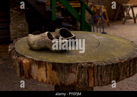 Netherlands, Zaanse Schans, wooden clog shoes on top of a wooden table - Stock Photo