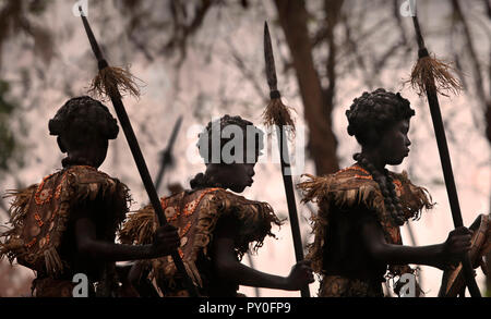 Three children wearing tribal African costumes on blurred background at Ati Atihan festival, Kalibo, Aklan, Panay Island, Philippines - Stock Photo
