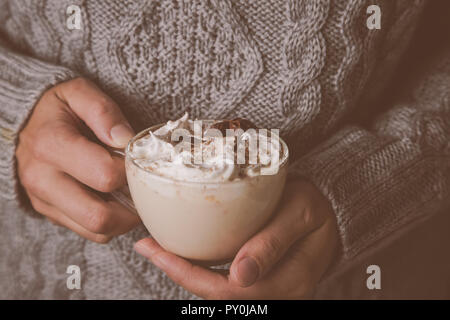 Hands holding cup of chai latte - Stock Photo